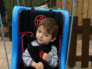 Gorgeous boy Layton in his special swing which we funded.